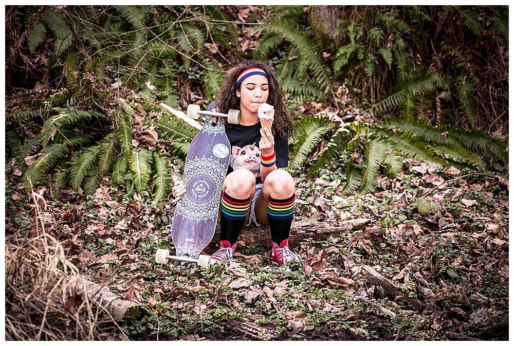Skater girl Avi posing in woods with longboard.