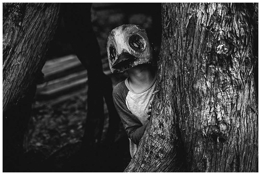 Kid in animal mask peeking out from behind a tree in the Pet Sematary.